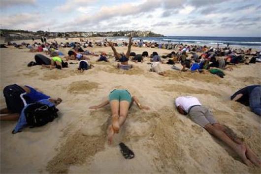 Активисти са заровили глави в пясъка като щрауси на плаж в Сидни. СНИМКА: 24 Часа