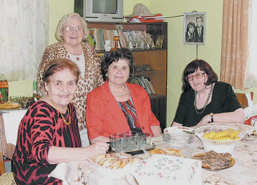 Домакинята Н. Марчева с помощта на приятелката си Ст. Маркова отрупа богата трапеза за колежките си С. Гебова и Б. Симеонова /отляво надясно/
