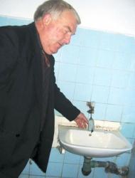 Директорът Д. Колев показва сапуните, вързани за чешмите, за да не си играят с тях учениците