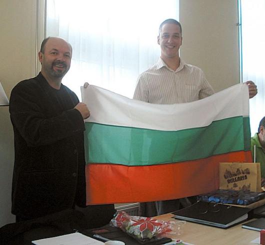 Директорът Емил Терзийски връчва подарък - българския трикольор, на колегата си от Холандия